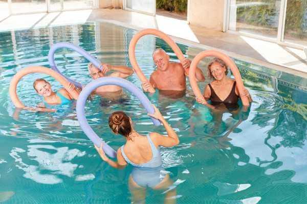 Instructora guiando a adultos mayores en clases de gimnasia acuática dentro de una piscina.