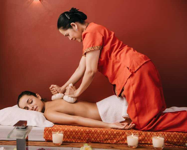 Mujer recibiendo masaje tailandés herbal para la espalda en un spa.