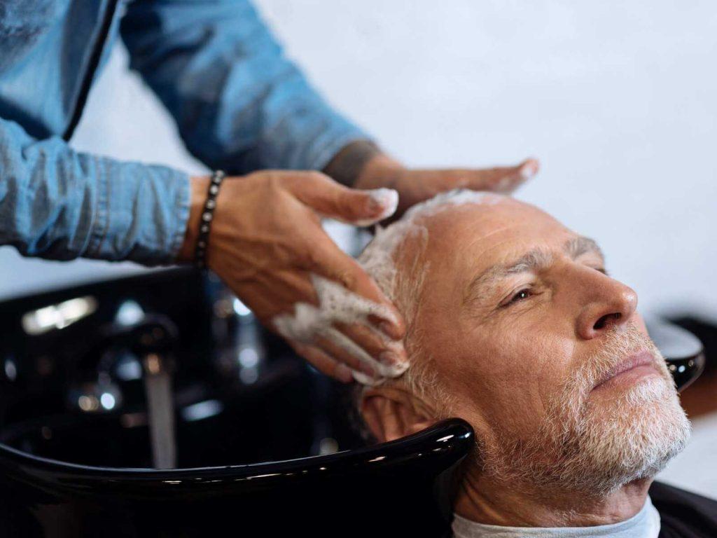 Hombre de tercera edad en un spa recibiendo tratamiento para reducir la caída del cabello y estimular su crecimiento.