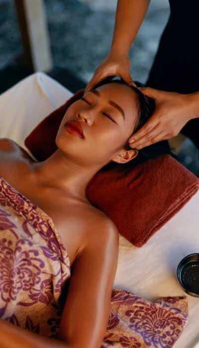 Mujer joven recibiendo una terapia con rotaciones y presiones en la parte superior y los lados de la cabeza.