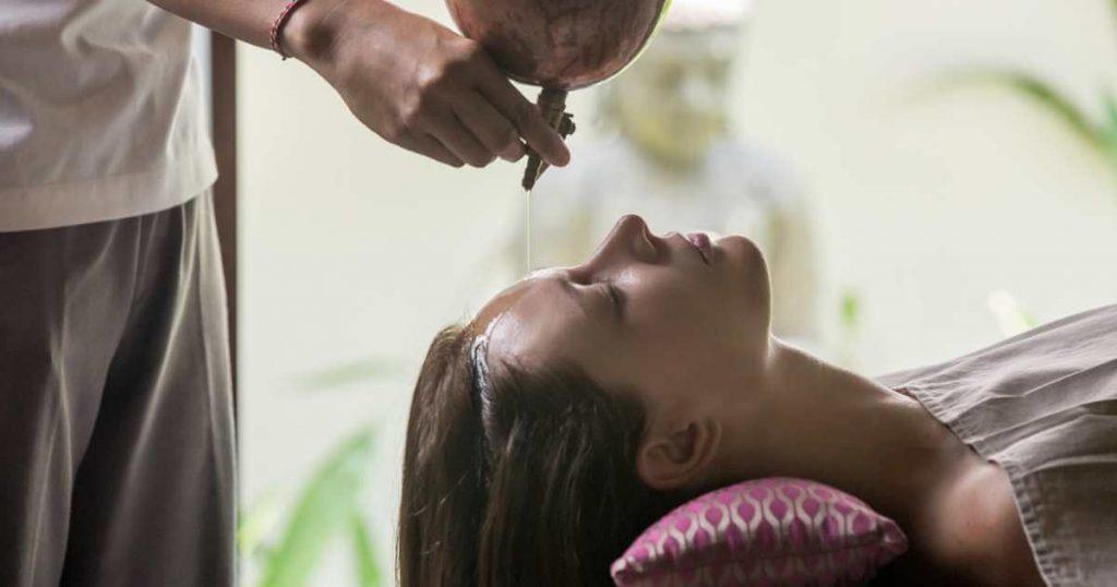 Terapeuta aplicando aceites naturales a la frente y cuero cabelludo de una mujer joven antes del masaje craneal.