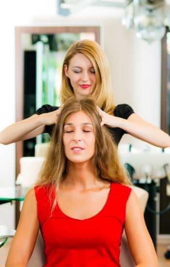 Mujer en centro estético recibiendo roces y presiones como tratamiento capilar para eliminar tensiones.