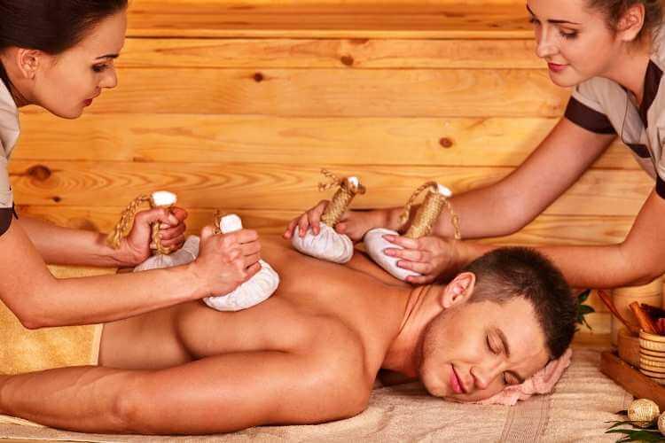 Masaje con pindas a cuatro manos aplicado en la espalda de un joven.