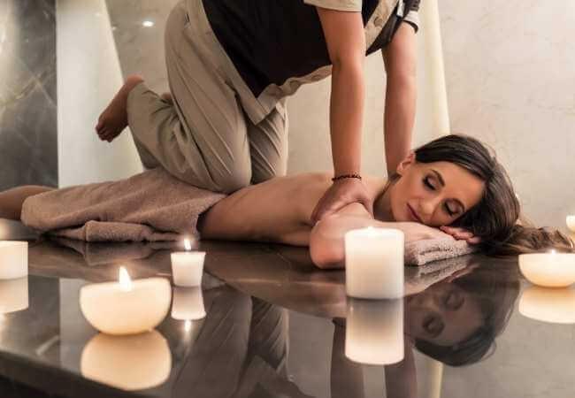 Mujer acostada boca abajo sobre una mesa de masaje mientras la terapeuta realiza presiones en el área más baja de la zona lumbar con sus rodillas.