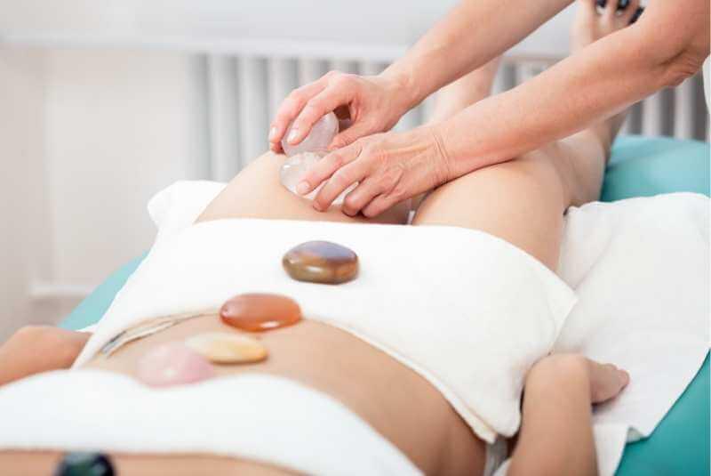 Terapeuta realizando amasamientos y fricciones con piedras de cuarzo para reducir la celulitis en el musla de una clienta.