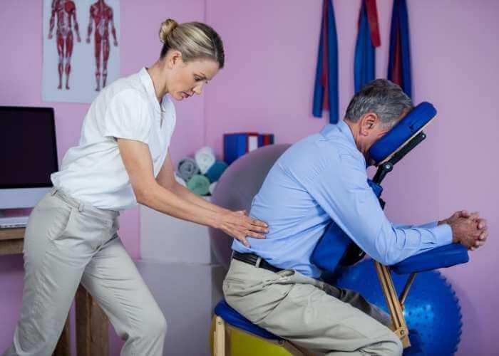 Hombre maduro sentado en una silla de para masaje de espalda recibiendo fisioterapia lumbar en una clínica.