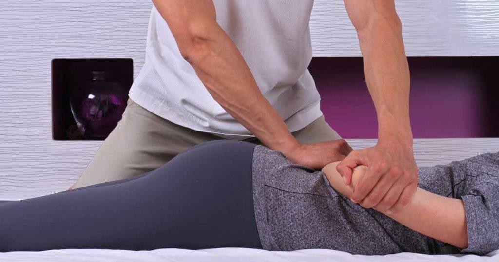 Terapeuta realizando estiramientos y movilizaciones en el brazo derecho de una cliente.
