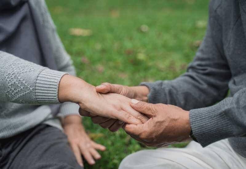 Un hombre de la tercera edad realizando un masaje en las articulaciones de una de las manos de su esposa.