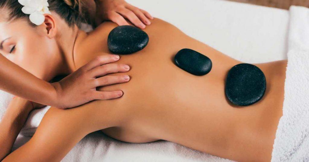 Mujer recibiendo masaje en los hombros mientras tiene colocadas piedras volcánicas calientes sobre la columna.