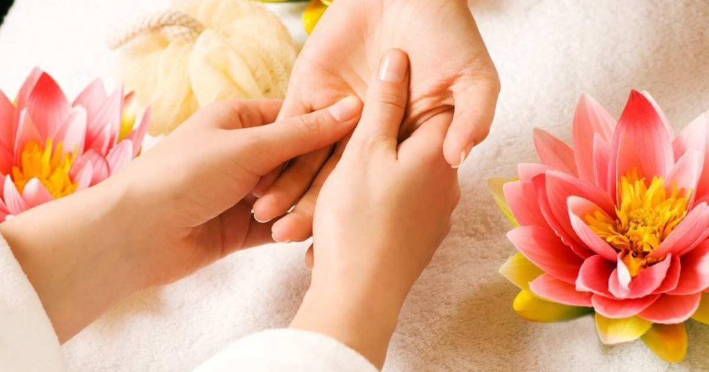 Terapeuta realizando un masaje en las palma de una clienta de spa.