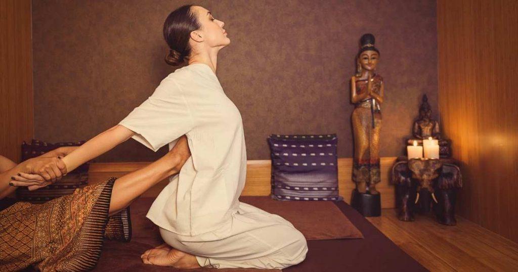 Mujer en spa durante un masaje tailandés. Está arrodillada con la espalda erguida mientras la terapeuta realiza presión con su pie en el centro de su espalda y hala sus brazos suavemente hacia atrás para estirar su columna.