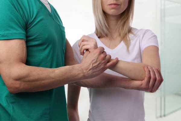 Mujer recibiendo masaje cyriax descontracturante con movilizaciones para la muñeca.