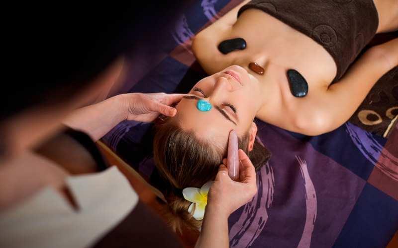 Masaje de pecho y rostro con piedras estáticas y un rodillo de cuarzo siendo deslizado sobre la frente de una paciente durante. La clienta tiene una piedra entre las cejas y tres colocadas sobre cada clavícula y la base del cuello.