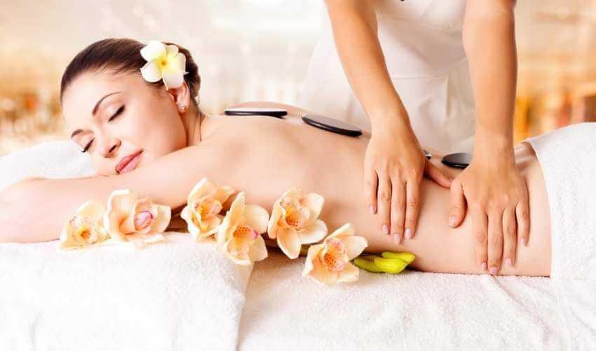 Mujer recibiendo masaje lumbar manual en los costados mientras tiene colocadas piedras calientes sobre toda la columna.