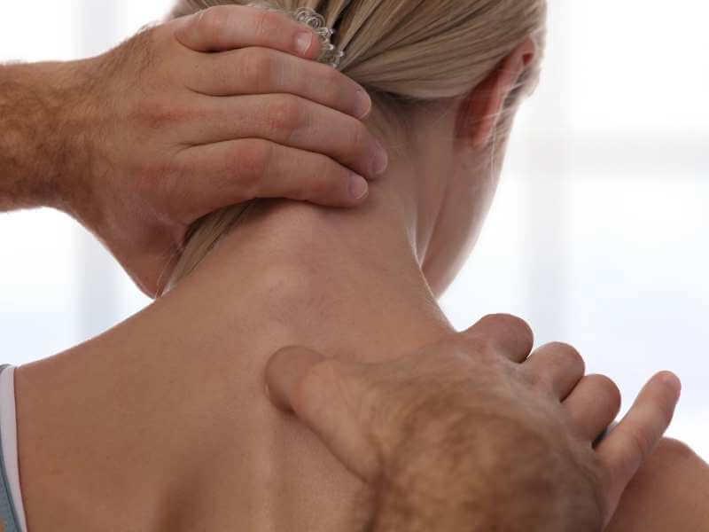 Terapeuta realizando tratamiento de digitopuntura en las vértebras de la espalda superior y cuello de una mujer.
