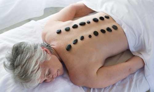 Mujer de la tercera edad con una hilera de piedras pequeñas de obsidiana colocadas a cada lado de su columna para aliviar malestares de la espalda.