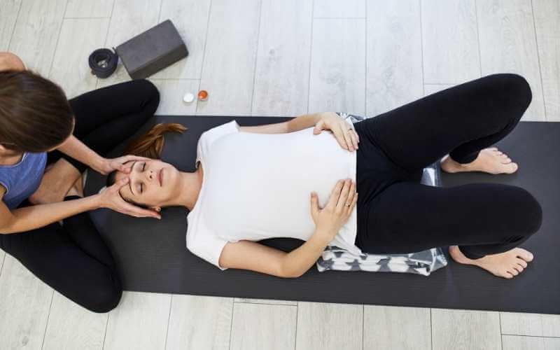 Embarazada acostada sobre una colchoneta y un cojìn para levantar su pelvis mientras recibe un masaje facial.