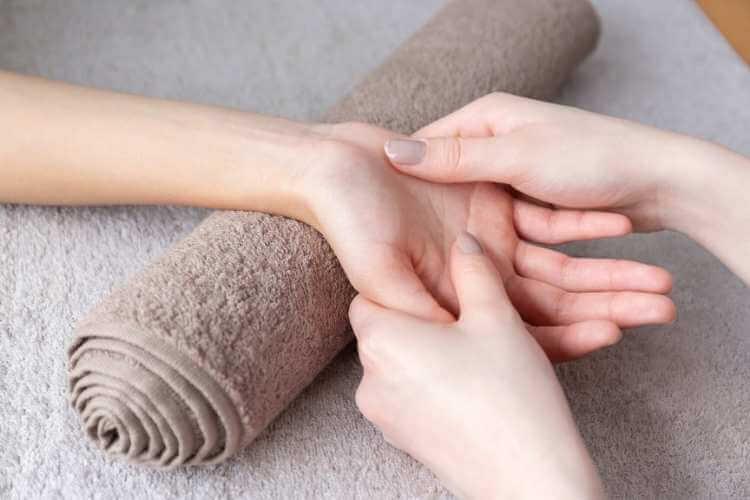 Mujer recibiendo masaje en la palma de una mano, con su muñeca apoyada sobre una toalla enrollada.