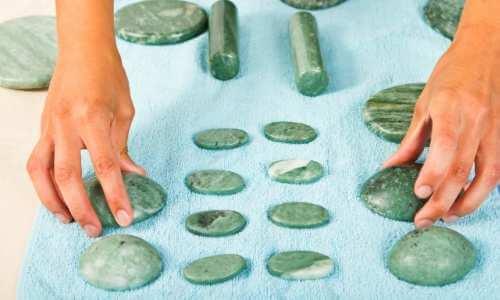 Variedad de tamaños de piedras y rodillos de jade para aplicar durante una terapia geotermal.