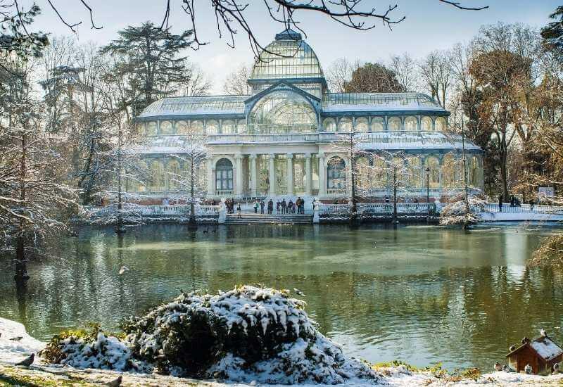 El Palacio de Cristal en un día de invierno con parte de la laguna frente al edificio con sus aguas congeladas.