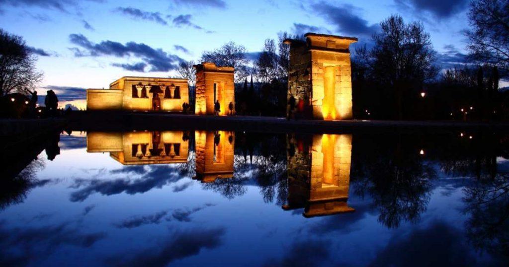 Vista panorámica nocturna del Templo de Debod en Madrid iluminado de noche, siendo reflejado en el estanque debajo de las estructuras.