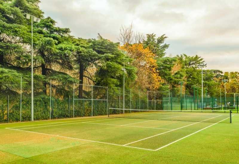 Una cancha de tenis del Parque de El Retiro, uno de los lugares mejores en Madrid para atletas aficionados, rodeada por árboles y con más canchas para otros deportes a la par.