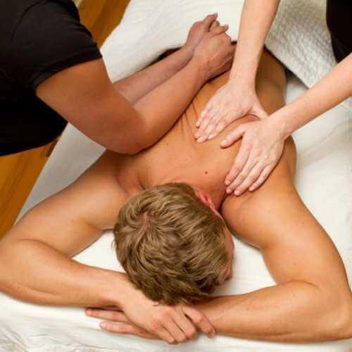 Dos terapeutas realizando masajes descontracturante simultáneos en la espalda de un joven. Una de ellas amasa el hombro y la espalda alta con las manos, mientras la otra presiona desde el otro hombro hasta la zona lumbar con los antebrazos.