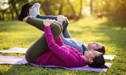 Hombre y mujer practicando estiramientos para las piernas en el parque.