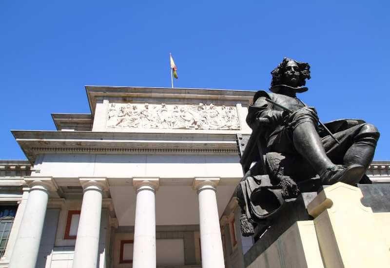 Fotografía de la estatua frente a la entrada del Museo del Prado y parte de la fachada, mostrando un mural esculpido sobre la entrada y la bandera de España alzada en un asta sobre el techo del museo.
