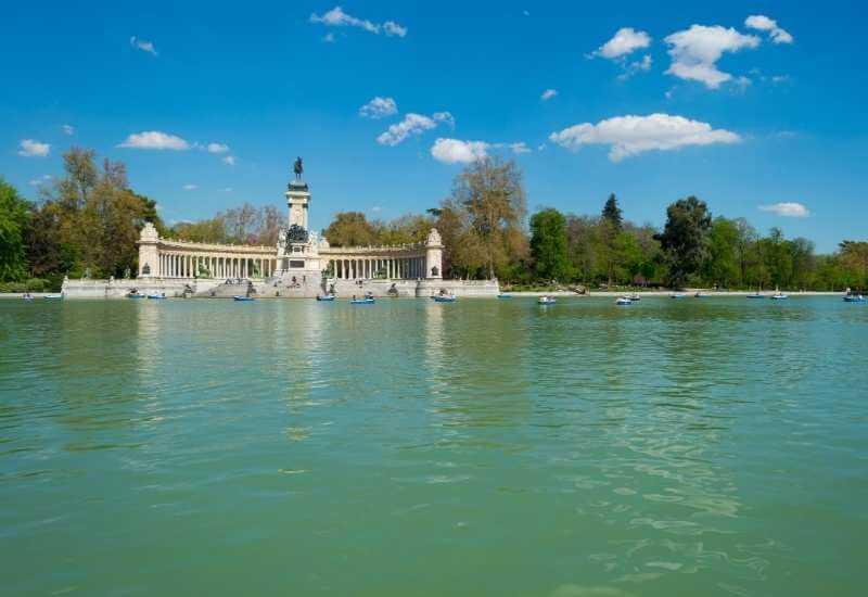 Vista panorámica desde lejos del Estanque Grande en Madrid. Vemos el monumento a Alfonso XII y la Fuente Egipcia al fondo, con personas partiendo en piraguas y botes de remo.