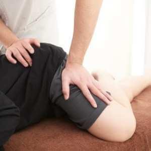 Terapeuta guiando a paciente para realizar un estiramiento y presiones para relajar los músculos de la pierna, glúteo y cadera izquierda.