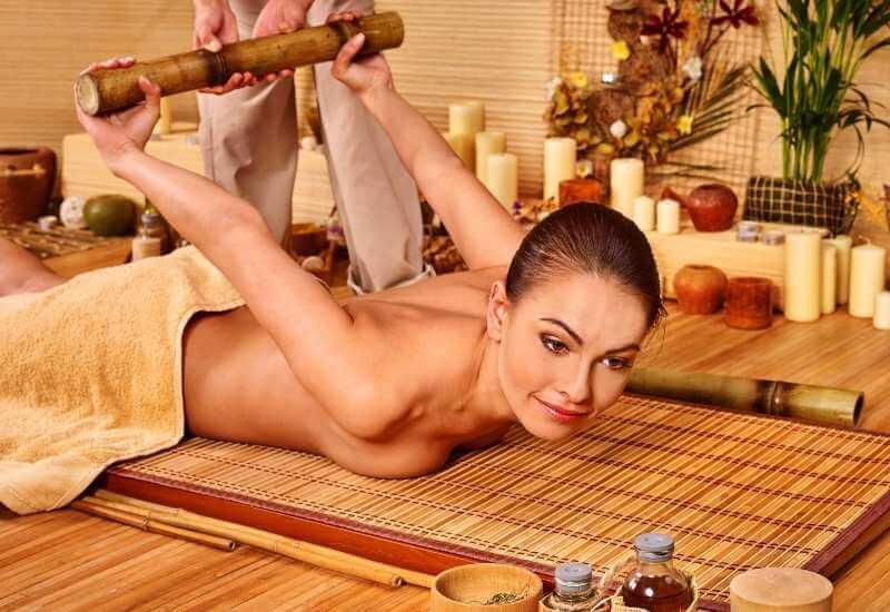 Mujer recibiendo masaje con cañas de bambú estilo Thai. La masajista estira los brazos, hombros y espalda de su clienta al jalar de una caña de bambú que su clienta sostiene con ambas manos detrás de su espalda.