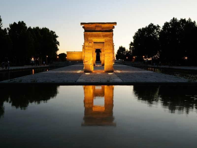 Vista frontal de los portales del Templo de Debod durante la puesta del sol, uno de los mejores lugares en Madrid para apreciar la caída de la noche.