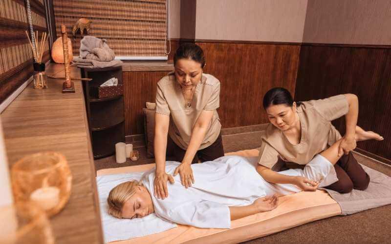 Masaje tailandés a cuatro manos en que una joven está acostada boca abajo sobre una colchoneta, con una terapeuta realizando amasamientos en la espalda mientras la otra realiza estiramientos para una pierna y presiones para la parte superior del muslo.