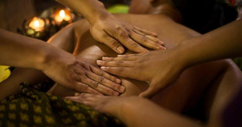 Mujer recibiendo masaje relajante a cuatro manos en la espalda. Las manos de las terapeutas de colocan alternadas para presiones sobre la columna con los dedos extendidos.