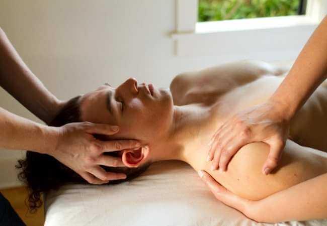 Hombre recibiendo terapia para cabeza y hombros simultáneamente durante un masaje a 4 manos.