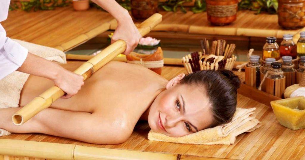 Mujer en spa acostada boca abajo mientras masajean su espalda rodando una caña de bambú.