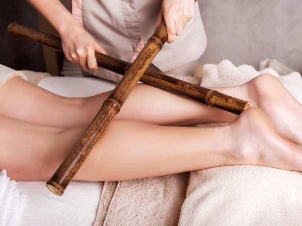 Terapeuta descontracturando y drenando las pantorrilas de una clienta durante una sesión de bambuterapia.
