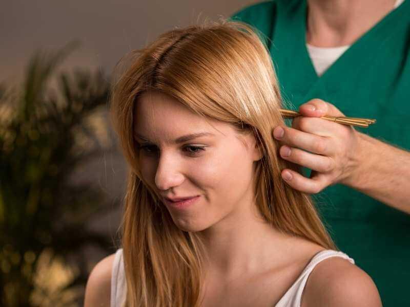 Terapeuta haciendo deslizamientos y presiones suaves a la parte trasera de la cabeza de una joven con palillos de bambú.