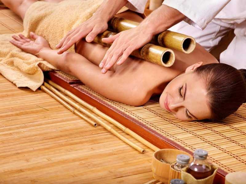 Mujer acostada boca abajo con dos cañas de bambú gruesas colocadas verticalmente y en paralelo sobre su espalda. La masajista presiona en las cañas para descontracturar y equilibrar la energía.