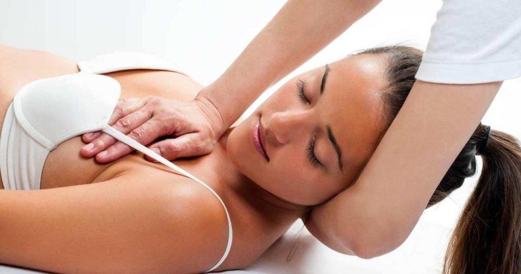 Mujer recibiendo presiones con las palmas en el pecho como tratamiento relajante y linfático.