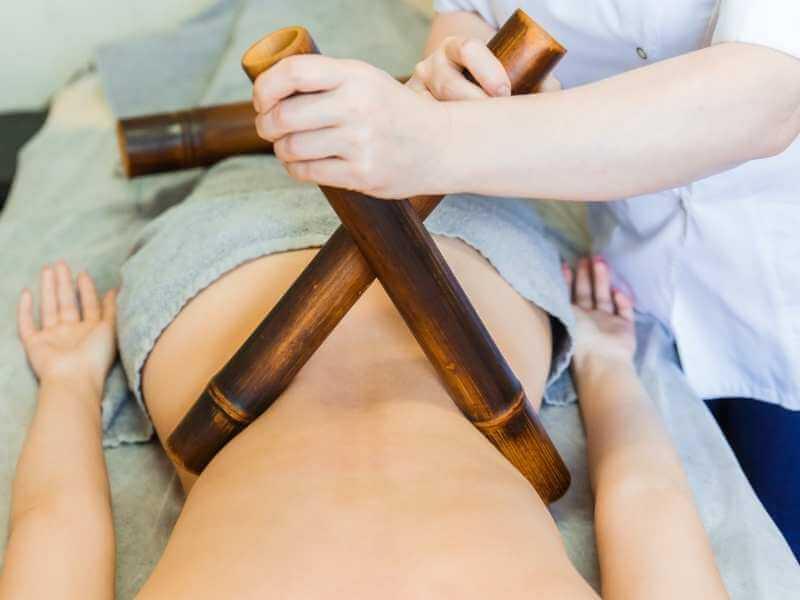 Masajista realizando presiones a cada lado de la cintura de su clienta con cañas de bambú para reducir talla.