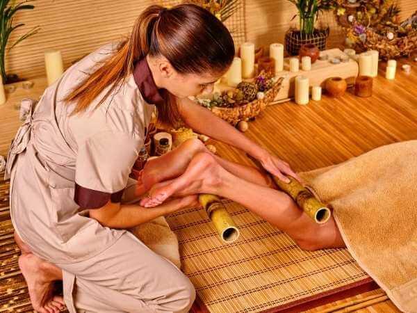 Masajista rodando rodillas de bambú en la parte trasera y frontal de desde las rodillas hasta los tobillos de ambas piernas de su clienta en un masaje con cañas de bambú.