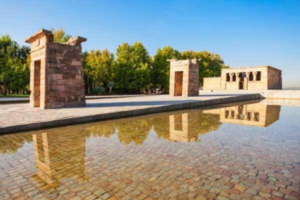 Vista panóramica del Templo de Debod en Madrid durante el día, donde se aprecian las piedras del fondo del estanque que rodea la estructura principal.