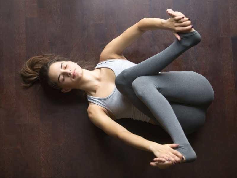 Mujer realizando una pose de estiramiento. Yace acostada con sus piernas dobladas encima de su torso y cruzándolas a partir de las rodillas para estirar sus pantorrillas con un movimientos diagonales mientras tira levemente de sus pies.