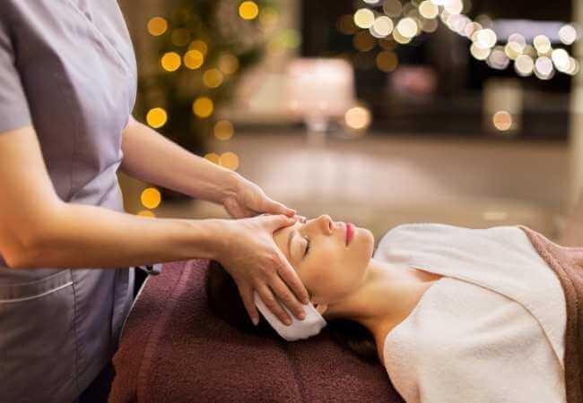 Mujer acostada en una camilla recibiendo presiones en la frente para aliviar dolores de cabeza y sinutsitis.