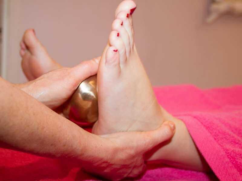 Masajista rodando una bola de oro por la planta del pie de una clienta.