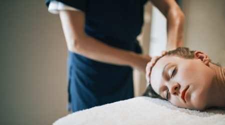 Mujer acostada en camilla recibiendo un masaje relajante manual en la coronilla.