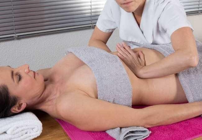 Masajista presionando los costados del abdomen hacia al centro con sus palmas mientras realiza un masaje reductor en una clienta.