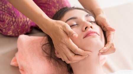 Mujer joven recibiendo presiones debajo de la quijada para aliviar dolores de la quijada y muelas.